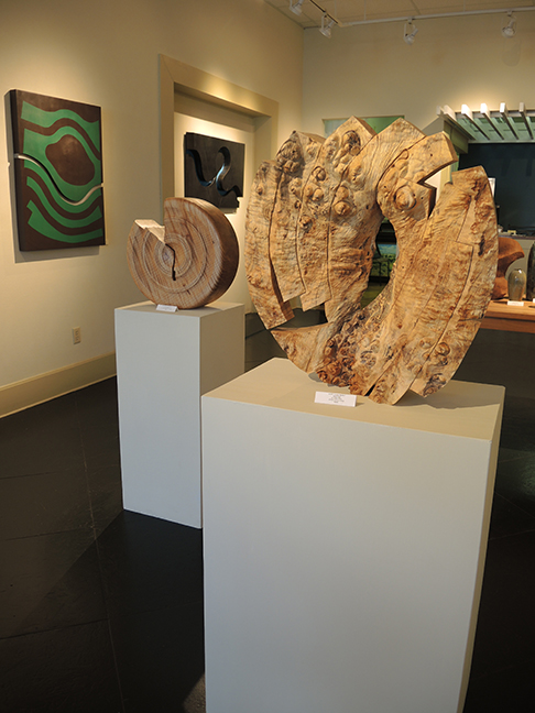 Wood sculptures by Robyn Horn and steel work by Robert Fogel on wall at Justus Fine Art Gallery - July 2017